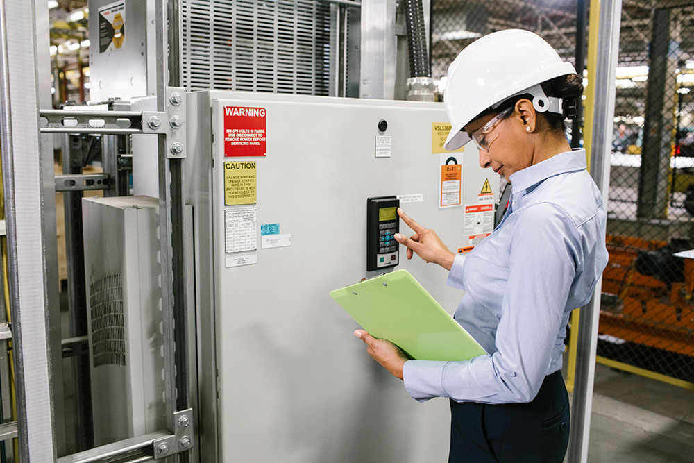 Energy manager standing with clipboard at variable frequency drive