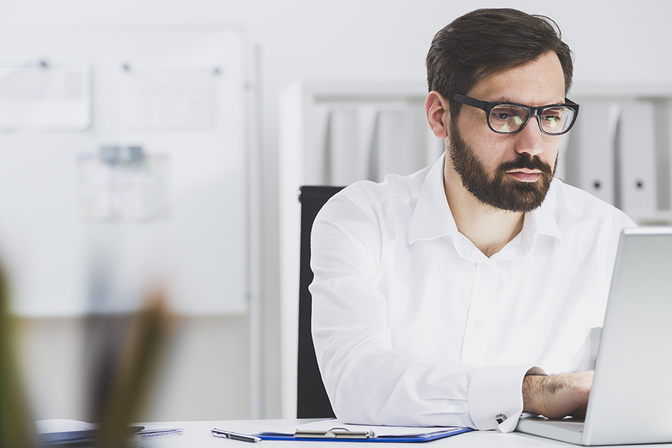 man using work laptop at clean office
