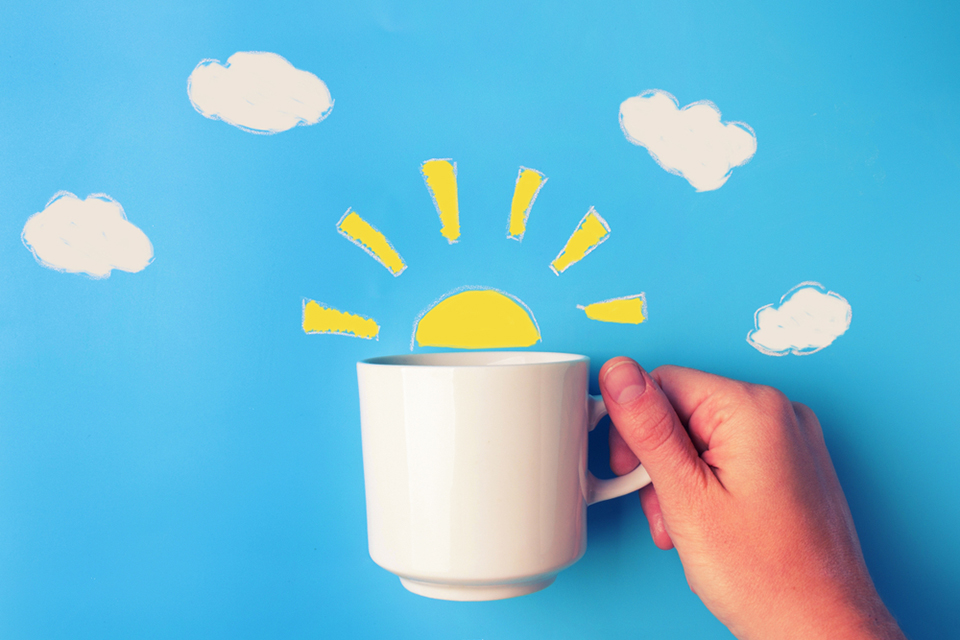 graphic of coffee cup with sunrise peaking from the cup