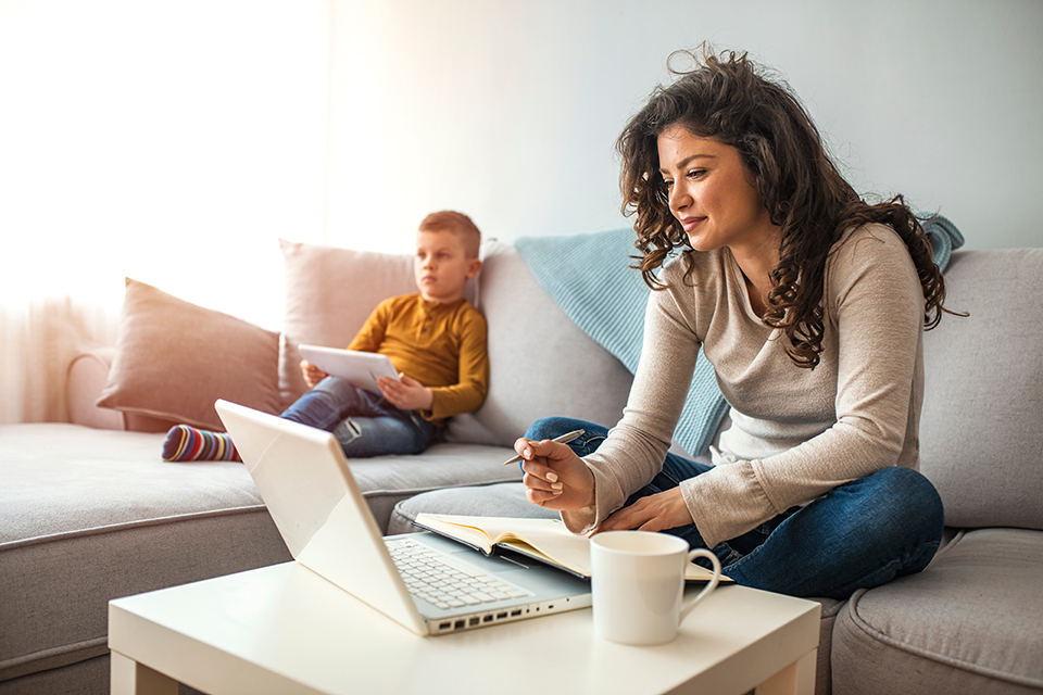 mother working from home on sofa beside young son