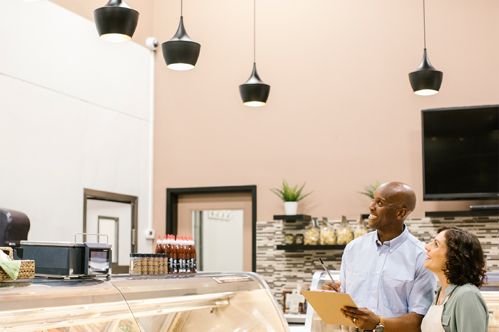 Energy manager and small business owner examining lighting solutions in her cafe
