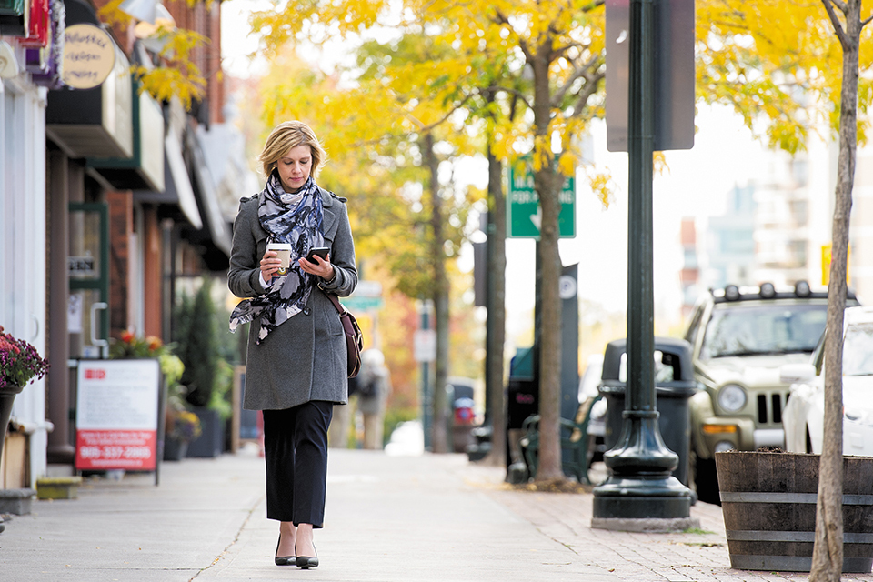 A woman walking down an avenue in autumn